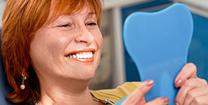 woman checking her straight teeth in the mirror