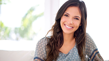 Lake Forest woman sitting on couch, smiling