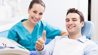 man on dental exam chair giving a thumbs up