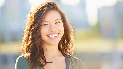 woman standing under sunlight, smiling