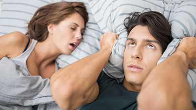 man covering ears because of wife snoring